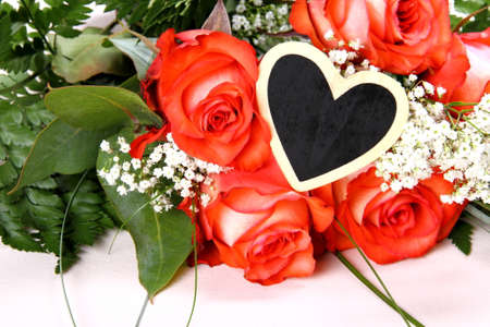 Red roses with writing board in heart shape, close up photo
