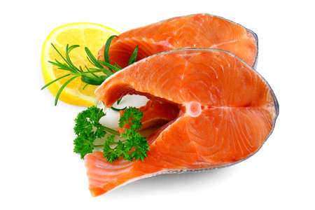 Two salmon steaks with lemon and herb, isolated photo