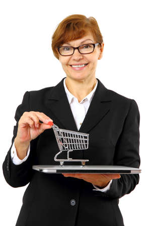 Mature red haired business woman with shopping cart, laptop, isolated Stock Photo - 24231267