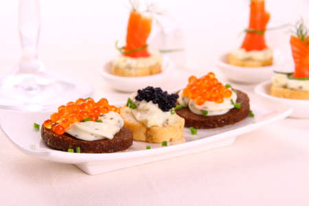 Red and black caviar on bread chunks as snack, close up photo