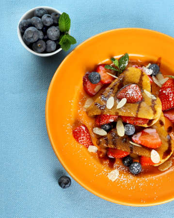 Two pancakes hearts with strawberry, blueberries  and almond slivers photo