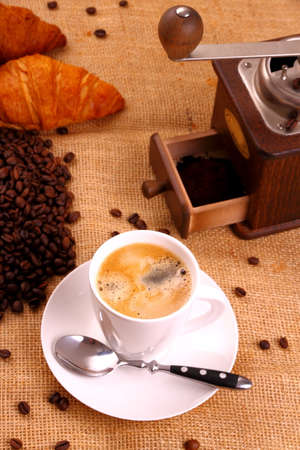 Coffee in white cup and coffee mill photo