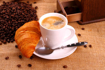 Coffee in white cup and croissant photo