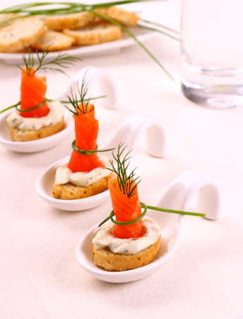 Smoked salmon roll on white bread and remoulade, close up photo