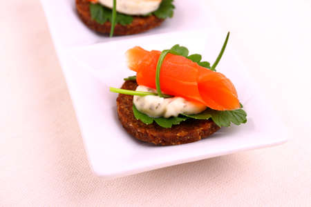 Smoked salmon roll on pumpernickel bread with remoulade, close up photo