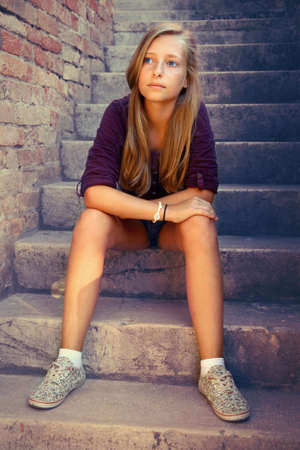 Sad girl with blue eyes sitting at stone brick stairs, soft focus photo