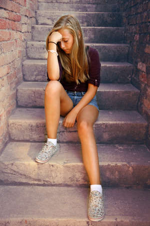 Thoughtful girl with blue eyes sitting at stone brick stairs, soft focus photo