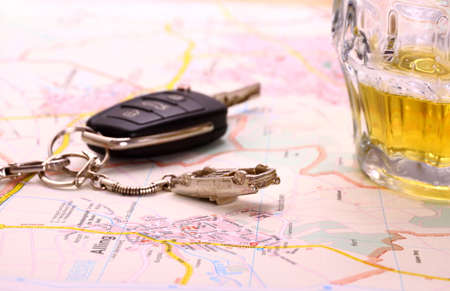 Car key with accident and beer mug on map, close up photo