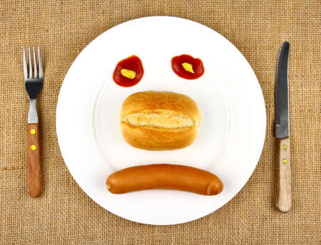 Sausage with bun on the plate as sad Face, top view