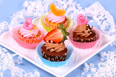 Assorted cup cakes with angel, heart, tangerine, strawberry, close up photo