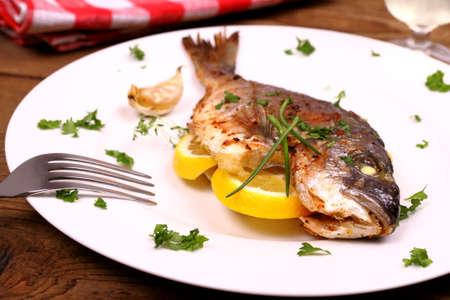 Grilled sea bream fish, lemon on white plate, soft focus photo