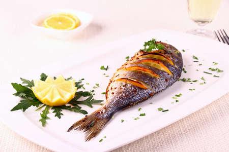 Grilled sea bream fish, lemon, arugula on white plate, horizontal photo