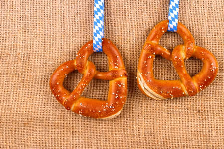 Two pretzel in heart shape on jute background, top view photo
