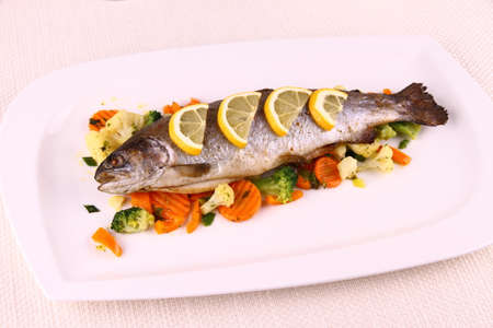 Grilled whole trout with vegetables and lemon, top view photo