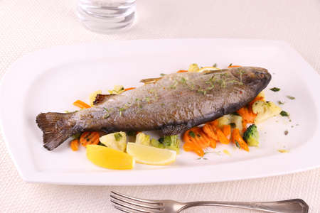 Fried whole trout with vegetables and cutlery, horizontal photo