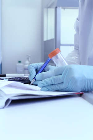 Lab technician write test results in laboratory notebook, soft focus