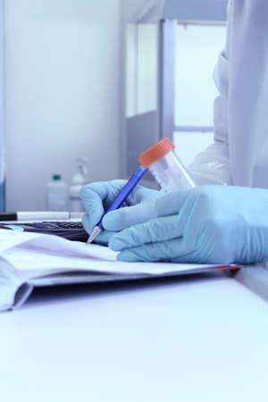 Lab tekniker skrivtestresultat i laboratorium anteckningsbok, mjukt fokus