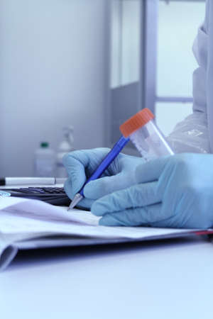 Hand of chemist with pen writing down observations in laboratory