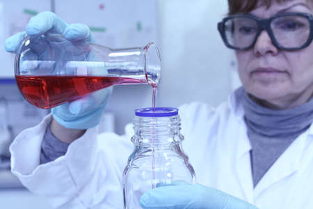 phlebotomist: Lab expert forgets red liquid from test tube for test Stock Photo