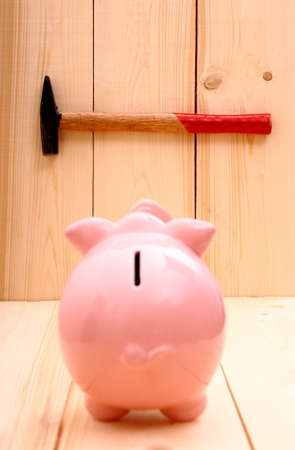 Funny pink piggy bank and hammer in focus on wood background photo