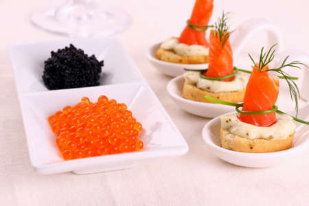 Red caviar and smoked salmon rolls on white bread chunks, top view photo