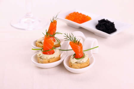 Smoked salmon rolls on white bread chunks, top view photo