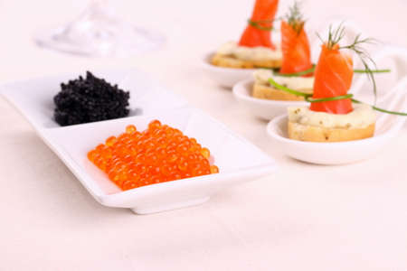 Red caviar, smoked salmon rolls on white bread chunks, top view photo