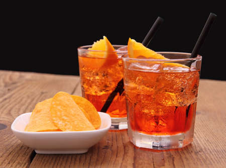 Spritz aperitif - two orange cocktail with ice cubes, potato chips Stockfoto