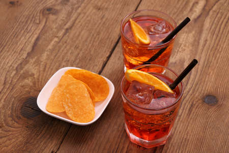 spritz: Spritz aperitif - two orange cocktail, ice cubes, potato chips, top view Stock Photo