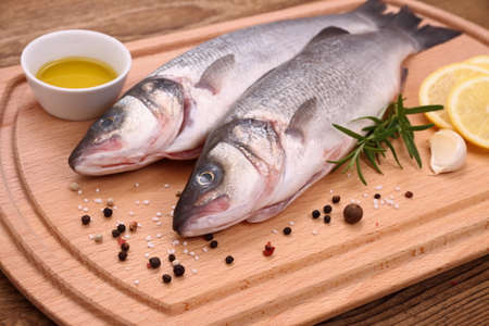 bass fish: Two fresh sea bass fish on cutting board with ingredients, close up Stock Photo