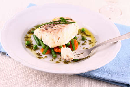 Cod fillet on fork with green beans, peas, parsley, olive oil, close up