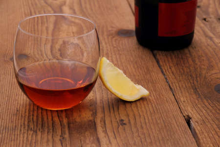 drunks: Luxury Cognac in decorative glass on wood with lemon, close up
