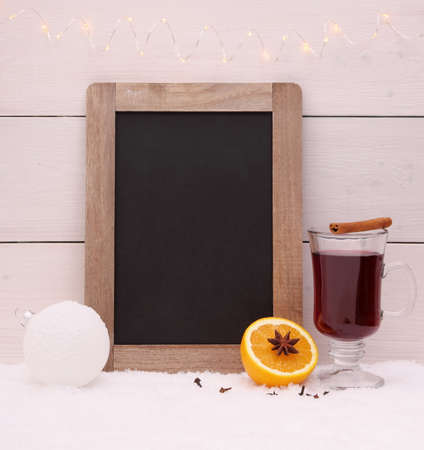 Chalkboard, mulled wine, orange and spice on snow photo