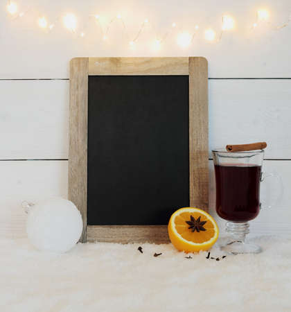 Chalkboard, mulled wine, orange, spice on snow and wire lights photo