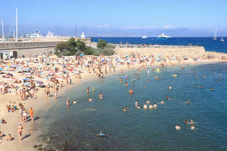 cote d'azur: ANTIBES, FRANCE - AUG 27, 2014: People relaxing on the public beach as background