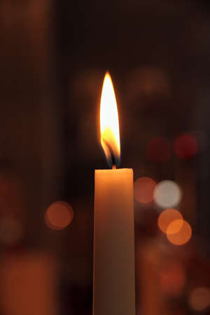 One candles in church as bokeh background photo