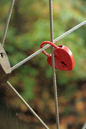 forbidden love: Red Lock in heart shape on rope bridge, vertical Stock Photo
