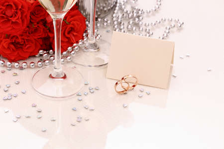 Two golden wedding rings with card, champagne glasses, red roses
