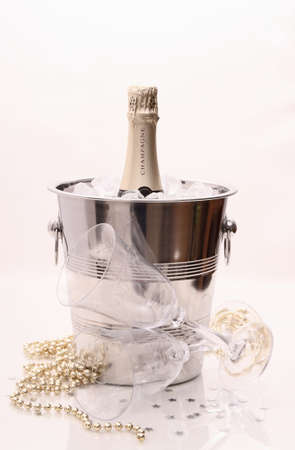 Champagne bottle in cooler and two champagne glasses on bright background photo
