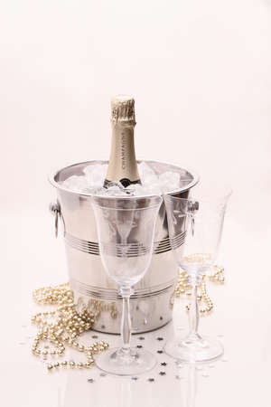 Champagne bottle in cooler, two champagne glasses on bright background photo