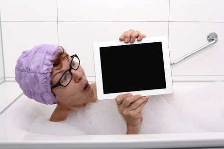 Enthusiastic woman in bathtub with tablet computers, close up Stock Photo