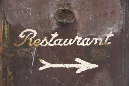 Old brown door with signature restaurant and arrow as Background photo