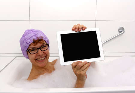 Entusiastiska mogen kvinna i badkaret med pekdatorer, närbild
