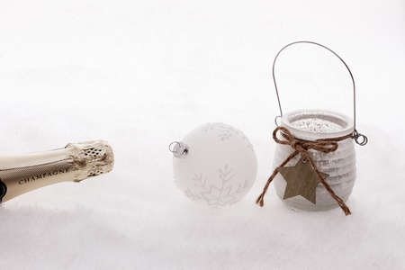 Christmas ball, wind candle, champagne bottle in snow, white edition photo