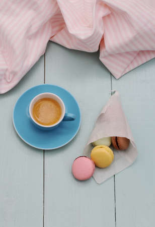 backing: Macarons in backing paper cornet and blue Espresso cup, top view Stock Photo