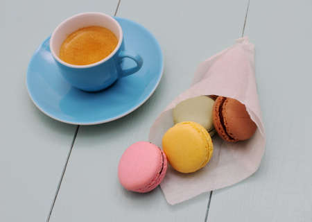 Macarons in backing paper cornet and blue Espresso cup, top view photo