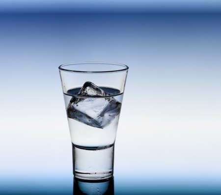 shooter drink: Short drink glass with clear liquid and ice cubes, blue background