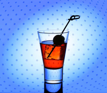 shooter drink: Short drink glass with red liquid and ice cubes, dotted background