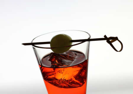 shooter drink: drink glass with red liquid, olive, ice cubes on gray background