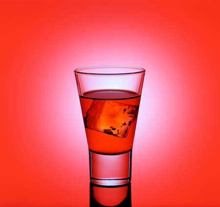 shooter drink: drink glass with red liquid and ice cubes on red background